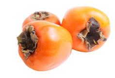 在白色隔绝的三个成熟柿子 库存图片