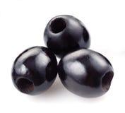 在白色隔绝的三颗黑橄榄 免版税库存照片