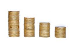 在白色隔绝的专栏的许多硬币 库存图片