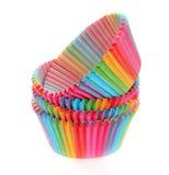 在白色隔绝的五颜六色的彩虹纸松饼或杯子蛋糕杯子 库存照片