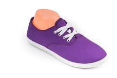 在白色隔绝的便宜的紫色体育鞋子 免版税库存图片