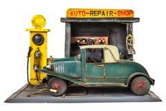 在白色隔绝的减速火箭的玩具汽车维修车间 免版税库存照片