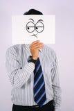 年轻在白色隔绝的商人佩带的疑义面具 图库摄影