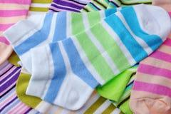 在白色隔绝的堆许多对五颜六色的镶边袜子 免版税库存图片