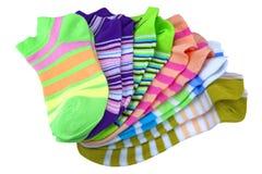 在白色隔绝的堆许多对五颜六色的镶边袜子 库存照片