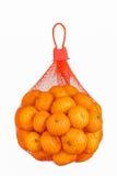 在白色隔绝的塑料滤网大袋的新鲜的桔子。 库存图片