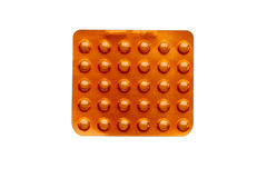 在白色隔绝的天线罩包装的橙色药片 库存图片