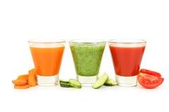 在白色隔绝的新鲜的蕃茄、红萝卜和黄瓜汁 库存照片