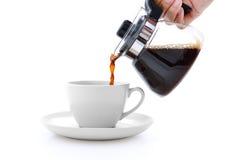 在白色隔绝的杯子的倾吐的咖啡 免版税库存图片