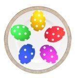 在白色隔绝的板材的五颜六色的复活节彩蛋 库存照片
