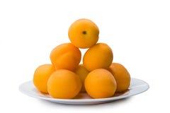 在白色隔绝的板材的黄色桃子切片 图库摄影