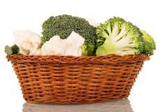 在白色隔绝的柳条筐的开花硬花甘蓝和花椰菜 免版税图库摄影