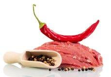 在白色隔绝的生肉牛肉,红色和黑胡椒 图库摄影