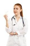 在白色隔绝的白色制服的年轻美丽的女性医生 库存照片