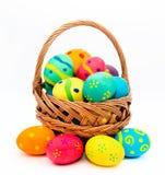 在白色隔绝的篮子的五颜六色的手工制造复活节彩蛋 图库摄影