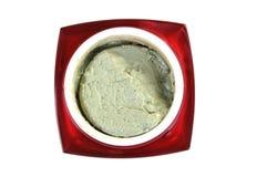 在白色隔绝的红色容器的有机绿色化妆奶油 免版税库存照片
