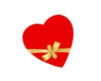 在白色隔绝的纸板心脏被包扎的金黄丝带弓 免版税库存照片