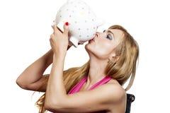 在白色隔绝的美好的少妇亲吻的piggybank 免版税库存照片