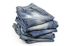 在白色隔绝的被折叠的老蓝色牛仔裤 包括的裁减路线 免版税图库摄影