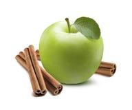 在白色隔绝的整个绿色苹果和肉桂条 库存照片