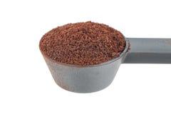在白色隔绝的黑塑料匙子的咖啡粉末 免版税库存照片