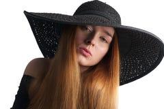 在白色隔绝的黑帽会议的美好的时装模特儿 免版税图库摄影