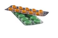 在白色隔绝的水泡的绿色和橙色药片 免版税库存图片