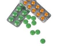 在白色隔绝的水泡的绿色和橙色药片 免版税图库摄影