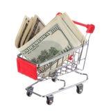 在白色隔绝的购物车的金钱。在台车的美金 免版税图库摄影