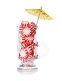 在白色隔绝的玻璃和鸡尾酒伞的薄荷糖。概念。红色镶边薄荷的圣诞节糖果 免版税库存图片