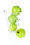 在白色隔绝的玻璃的新鲜的绿色苹果 免版税库存图片