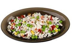 在白色隔绝的黑盘的菜混合 免版税库存照片