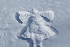 在白色雪一个孩子的版本记录以拍动它的翼的天使的形式 库存图片