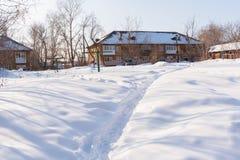 在白色雪的一条狭窄的道路,导致二层楼的房子 免版税库存照片