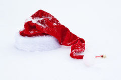 在白色雪的圣诞老人红色帽子 免版税图库摄影