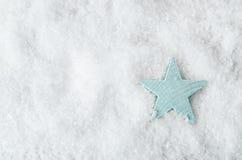 在白色雪的淡蓝的星从上面 图库摄影