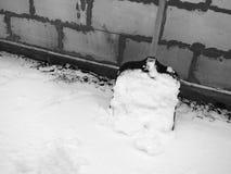 在白色雪的雪铁锹在砖墙的背景 免版税库存照片