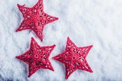 在白色雪背景的三个美丽的不可思议的葡萄酒红色星 冬天和圣诞节概念 免版税图库摄影