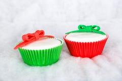 在白色雪背景的不同的圣诞节杯形蛋糕 库存照片