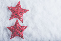 在白色雪背景的两个美丽的不可思议的葡萄酒红色星 冬天和圣诞节概念 免版税图库摄影