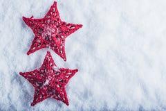 在白色雪背景的两个美丽的不可思议的葡萄酒红色星 冬天和圣诞节概念 免版税库存图片