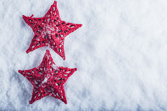 在白色雪背景的两个美丽的不可思议的葡萄酒红色星 冬天和圣诞节概念 库存图片