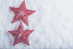 在白色雪背景的两个美丽的不可思议的葡萄酒红色星 冬天和圣诞节概念 图库摄影