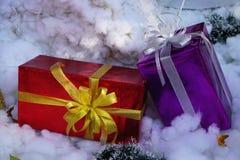 在白色雪背景的箔包装的礼物包裹 图库摄影