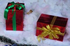 在白色雪背景的箔包装的礼物包裹 库存照片