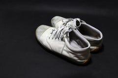 在白色颜色,但是它肮脏和阴沉的颜色的使用的运动鞋鞋子,在黑地板投入了对 免版税图库摄影