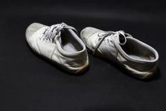 在白色颜色,但是它肮脏和阴沉的颜色的使用的运动鞋鞋子,在黑地板投入了对 免版税库存照片