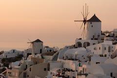 在白色风车的惊人的日落在Oia和全景镇到圣托里尼海岛,基克拉泽斯,希腊 免版税库存照片