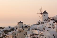 在白色风车的惊人的日落在Oia和全景镇到圣托里尼海岛,锡拉,希腊 库存图片