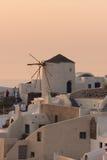 在白色风车的惊人的日落在Oia和全景镇到圣托里尼海岛,锡拉,希腊 免版税库存照片